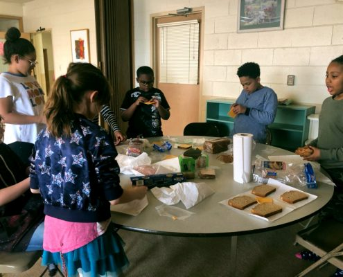 Upper Elementary students prepare lunches for community